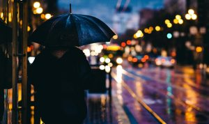 Young person walking down city street in the rain at nighttime